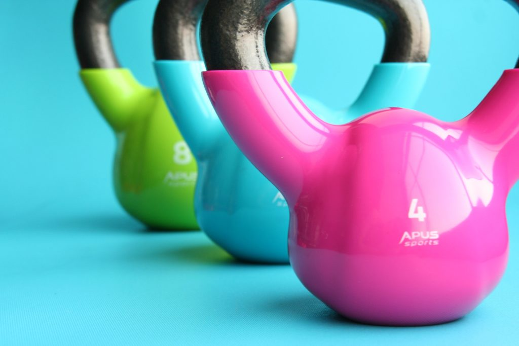 3 brightly coloured kettle bells on a blue background marketing for gyms
